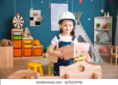 Little girl dressed as builder playing with take-apart house at home