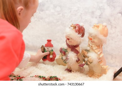 little girl dressed in a Christmas Santa Claus outfit looking at snowman ornaments whilst on a winter Christmas background