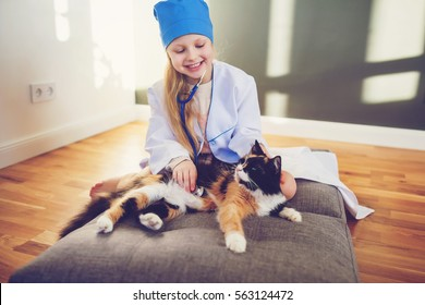 Little girl dressed as a doctor playing with home pet indoor