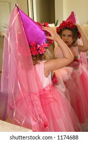 A little girl dressed up like a fairytale princess fixing her hat in a mirror.