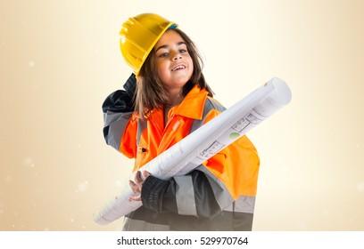Little girl dressed like laborer on ocher background