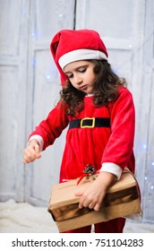 little girl dressed like a Santa Claus . in the hands of the baby gift