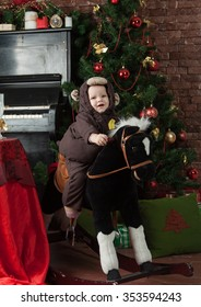 Little girl dressed as a monkey riding on a gurney-horse near a Christmas tree next to a lot of Christmas gifts
