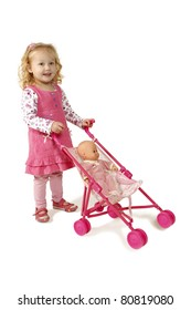 Little girl dressed in pink pushing a doll in a pram