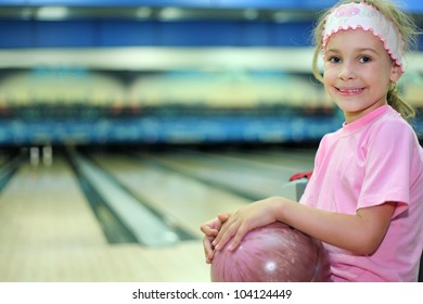 Little girl dressed in pink T-shirt sits and holds ball in bowling club