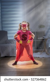Little girl dressed as super hero, she takes the pose with her hands on her hips. She is in her living room in the middle of a circle of light. Shot with flare