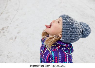Little girl dressed in winter clothes catching snowflakes with her tongue while walking through falling snow. Winter fun. Close up.