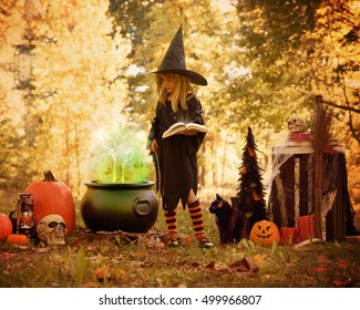 A little girl is dressed up in a witch costume outside with Halloween decoration props and a brew pot of magic. Use it for a childhood  imagination concept.