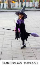 Little girl dressed as a witch riding a broom on Halloween.