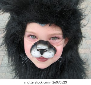 a little girl dresses up in a cat costume