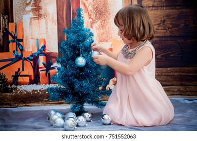 The little girl dresses up the Christmas tree