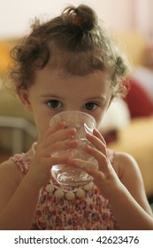 little girl drink water, focused at the camera with her big eyes