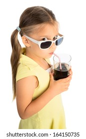 Little girl drinking cola beverage through a straw and looking at viewer over sunglasses skeptically, seen from high vantage point