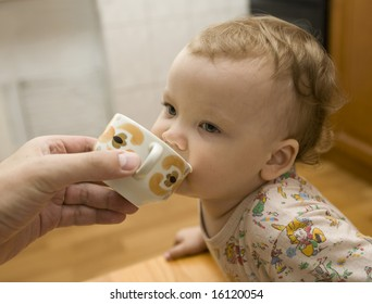 Little girl drinking to a cup