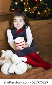 Little girl drinking a glass of milk at Christmas night