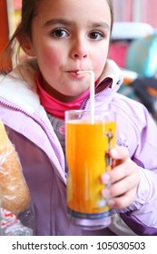 Little girl drinking juice using a straw