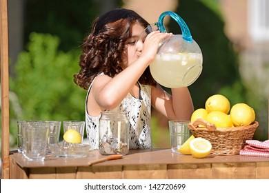 little girl drinking from lemonade pitcher