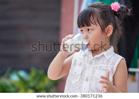 Little girl drinking milk at home, soft focus