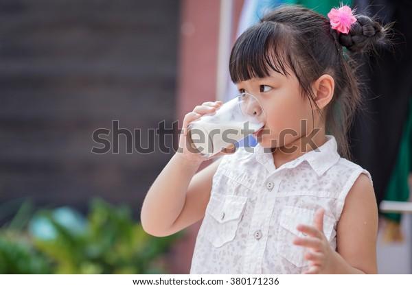 Little girl drinking milk at home, soft focus