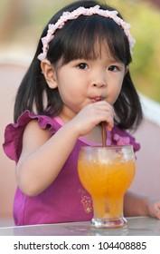 Little girl drinking orange juice