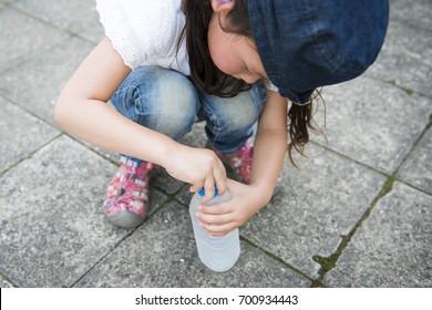 Little girl drinking water of plastic bottle