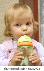 little girl drinks from a small bottle and with interest looks aside