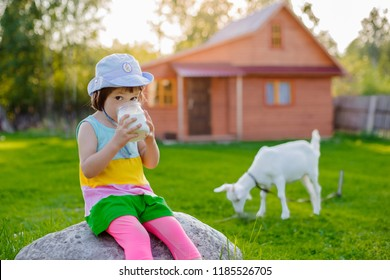 little girl drinks useful goat's milk at a house in a village in Russia in the summer on vacation. Lactose. Ecological natural product