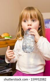 little girl drinks water from a bottle