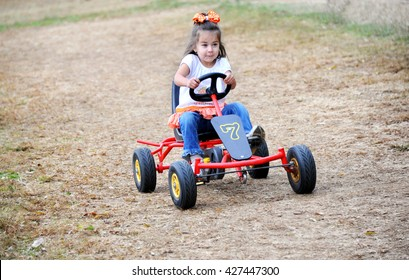 Little girl drives a go cart on a dirt track in Tennessee.  She has a determined look on her face as she gives it her all.