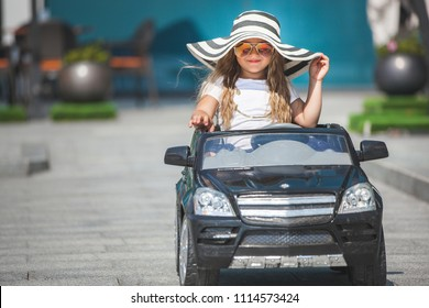 Little girl driving a toy car outdoor