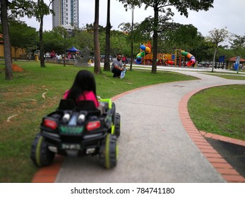 Little girl is driving a toy car in the park while being watched the father and little sister.