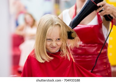 Little girl dry hair in the barber shop.