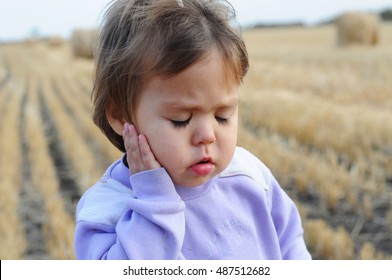Little girl with ear pain moaning holding hand on ear, child headache pain, health care concept, ear protection from cold, kid catch cold in cold season, hearing loss,