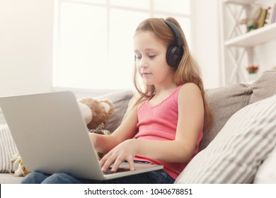 Little girl in earphones with laptop at home. Cute child doing homework on computer. Modern online education, communication and technology concept, copy space