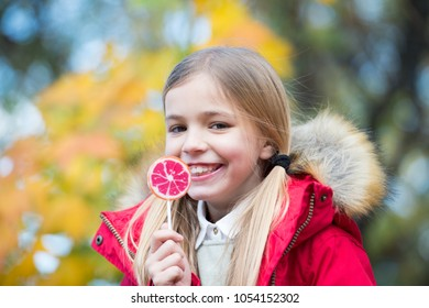 Little girl eat candy on stick, food. Child smile with lollipop, snack. Food, snack, dessert for small child on nature. Happy childhood and youth. Kid beauty, fashion, look.