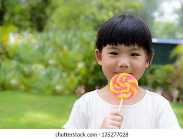 Little girl eat lollipop with smiling face