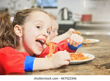 Little girl eat pasta in the kitchen table