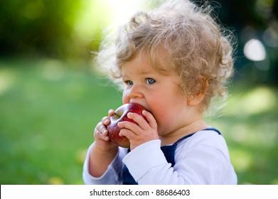 little girl is eating a apple