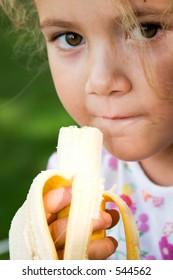 little girl eating a banana