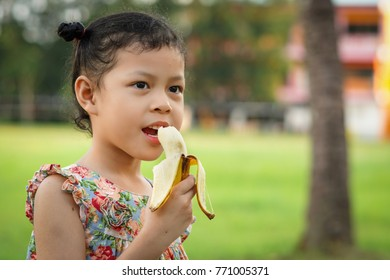 Little girl is eating banana