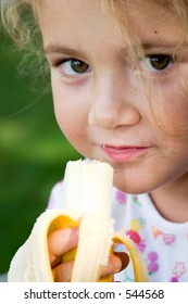 little girl eating a banana at the park