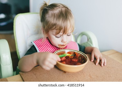 Little girl eating a beetroot soup indoors. Toddle enjoying the meal.