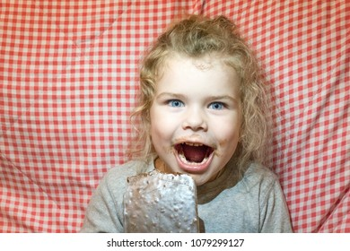 little girl is eating a big chocolate in a gold foil