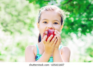 little girl eating a big red apple