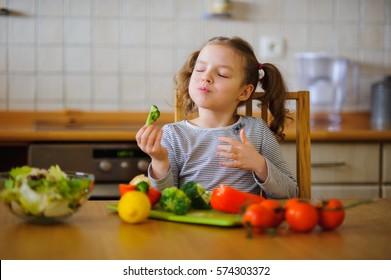Kleines Mädchen, das Broccoli isst. Sie sitzt am Küchentisch. Vor ihr eine Vielzahl von Gemüse und Kräutern. Auf dem Tisch steht eine Salatschüssel mit geschnittenem Gemüse. Alles sieht sehr appetitlich aus.