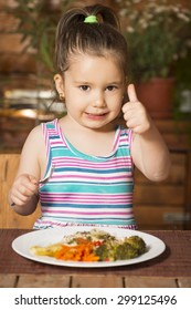 Little girl eating by itself broccoli, carrot and bell paper showing ok hand sign