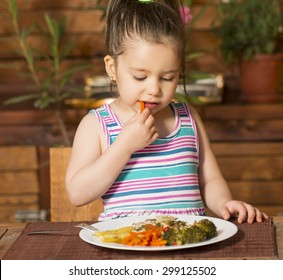 Little girl eating by itself broccoli, carrot and bell paper with hands
