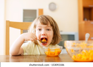Little girl eating carrot salad  in home