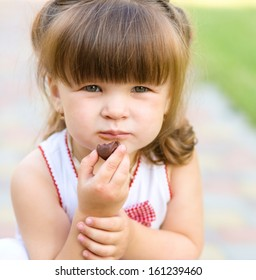 Little girl is eating chocolate candy, outdoor shoot