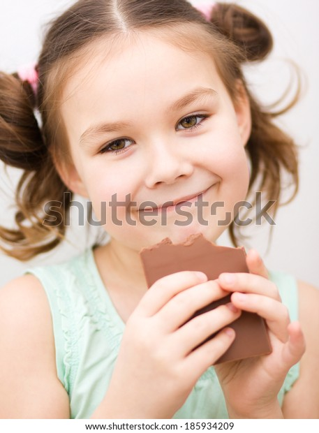 Little girl is eating chocolate candy